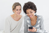 Smiling female friends reading text message on bed