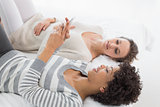 Relaxed female friends reading text message in bed