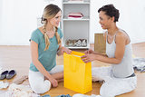 Two women sitting on floor with shopping bag