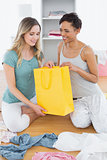 Smiling women sitting on floor with shopping bag