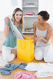 Two smiling women sitting on floor with shopping bag