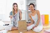 Smiling women sitting on the floor with shopping bag