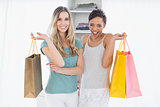 Cheerful women standing with shopping bags at home