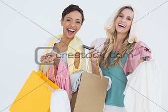 Portrait of cheerful women standing with shopping bags