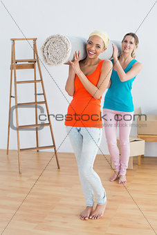 Female friends carrying rolled rug after moving in a house