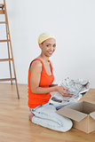 Happy young woman unwrapping boxes in new house