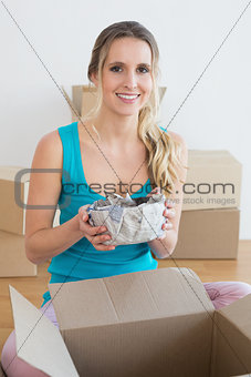 Woman unwrapping boxes in new house