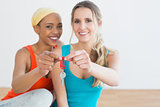 Portrait of two cheerful female friends with house keys