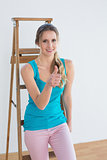 Woman gesturing thumbs up against ladder in a new house