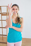 Woman gesturing okay sign against ladder in a new house