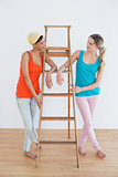 Female friends with a ladder in a new house