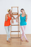 Female friends gesturing thumbs up against ladder in new house