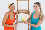 Friends with ladder choosing color for painting a room