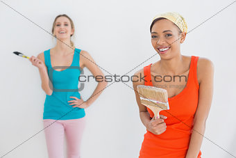 Portrait of two cheerful female friends holding paintbrushes