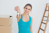 Woman holding out with key besides boxes in new house