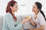 Happy female friends toasting wine glasses at home