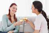 Happy young female friends toasting wine glasses at home