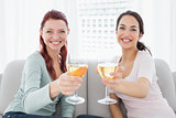 Happy female friends holding out wine glasses at home