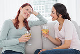 Female friends with wine glasses chatting on sofa at home