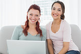 Relaxed young female friends using laptop at home