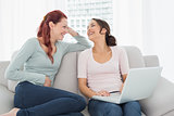 Cheerful female friends using laptop at home