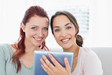 Close-up of two female friends using digital tablet
