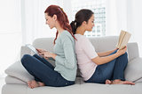 Female friends with digital tablet and book at home