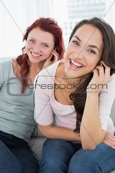 Cheerful friends listening music through earphones together
