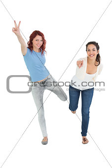 Two cheerful young female friends with hand gestures
