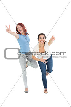 Cheerful young female friends with hand gestures