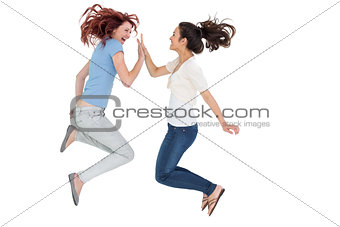 Happy young female friends playing clapping game