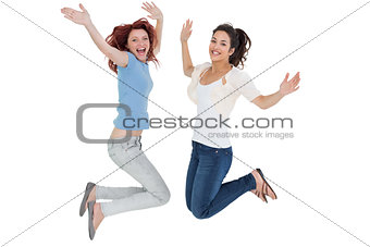 Portrait of two cheerful young female friends jumping