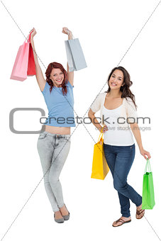 Two happy young female friends with shopping bags