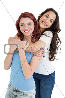 Young female embracing her friend from behind