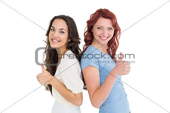 Portrait of two young female friends gesturing thumbs up