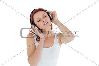 Beautiful casual woman enjoying music through headphones
