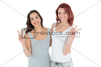 Portrait of two young female friends gesturing peace sign
