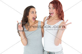 Portrait of two cheerful female friends gesturing peace sign