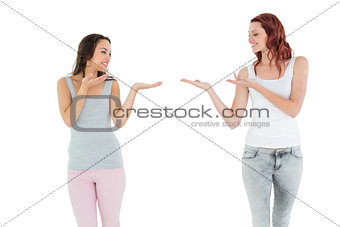 Two happy young female friends holding out their hands