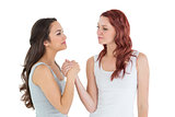 Two casual young female friends arm wrestling