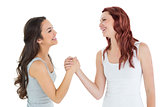 Two cheerful young female friends arm wrestling