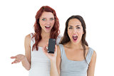 Shocked casual female friends with mobile phone