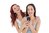 Smiling young female friends with mobile phone