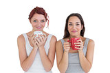 Two smiling young female friends with coffee cups