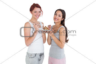 Two happy young female friends eating pastry together