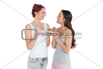 Cheerful young female friends eating pastry together
