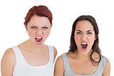 Close-up of two angry young female friends shouting