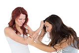Angry young woman pulling females hair in a fight