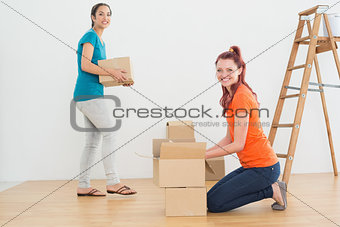 Portrait of two friends moving together in a new house