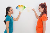 Cheerful friends choosing color for painting a room